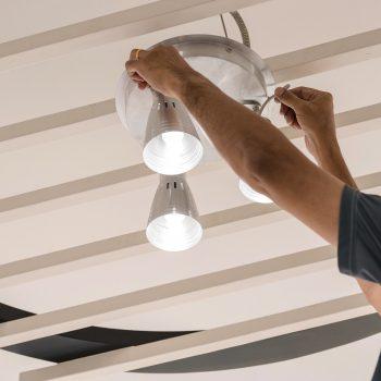 Engenheiros elétricos a instalar lâmpadas de teto no corredor